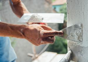 Ein Mann spachtelt einen Riss an der Fassade eines Hauses zu