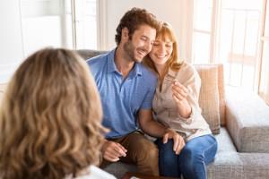 Ein glückliches Paar sitzt auf der Couch und freut sich über die Schlüssel zum neuen Zuhause