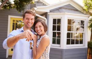 Ein glückliches junges Paar steht vor seinem neuen Haus und zeigt den Hausschlüssel