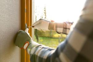 Ein Mann justiert die Stellschrauben eines Fensters