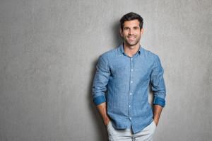 Ein Mann in Hemd steht lässig vor einer Wand