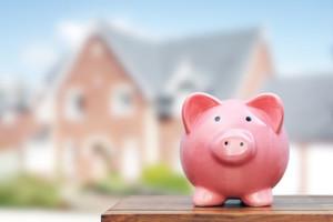Ein Sparschwein steht im Vordergrund, im Hintergrund sieht man ein Wohnhaus