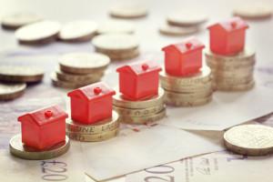 Rote Monopoly Häuser stehen auf ansteigenden Münzstapeln