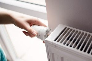 Nahaufnahme einer Hand, die den Thermostat einer Heizung dreht