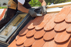 Ein Arbeiter tauscht Dachziegel auf einem Dach