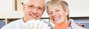 Älteres Paar hält Geldscheine und ein Modelhaus in der Hand