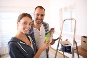 Ein junges Paar will Malerarbeiten angehen und hält einen Farbfächer in der Hand