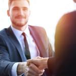 Zwei Personen in Businesskleidung begrüßen sich