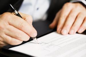 Ein Mann mit schwarzem Jacket unterschreibt einen Vertrag
