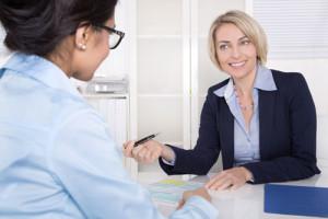 Eine Frau in Businesskleidung berät ihre Kundschaft am Bürotisch